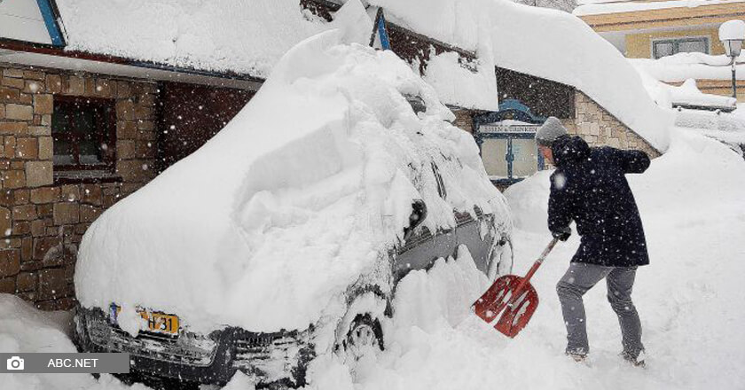A man shoveling his car out of the deep snow that buried it.