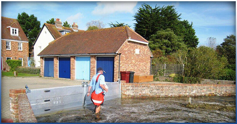 a person walking in flood, house protected by flood barriors