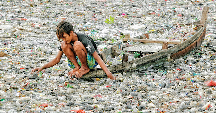 boy collecting many trash bottles from flood water