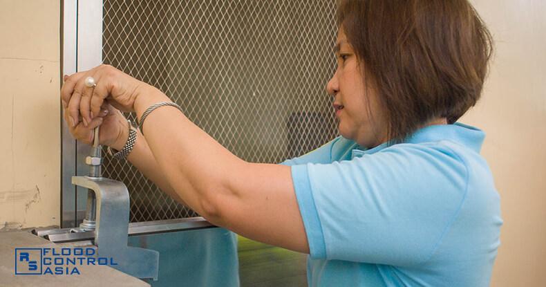 Flood Control Asia RS Ms. Gloria Chua installing the flood control RS demountable barrier