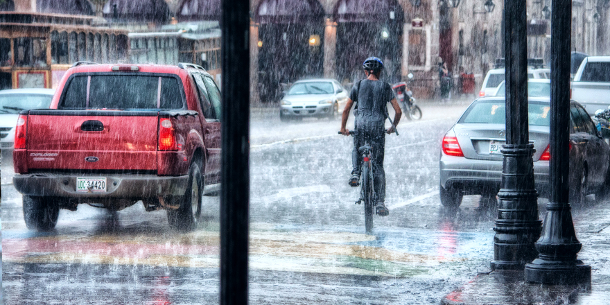 cars and man riding a bike in the rain